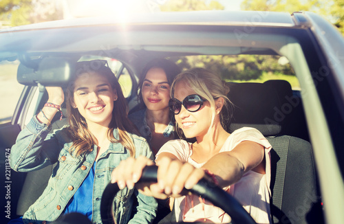 Poster summer vacation, holidays, travel, road trip and people concept - happy teenage girls or young women driving in car