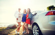 summer vacation, holidays, travel, road trip and people concept - happy teenage girls or young women near car at seaside - 221133830