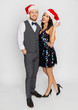 celebration, people and holidays concept - happy couple in santa hats at christmas or new year party