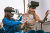 Technological developments. Nice young woman being in the virtual reality while sitting on the bed together with her daughter - 221135099