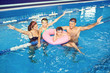 Leinwanddruck Bild - A happy family is smiling in a swimming pool indoors.