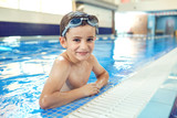 Little boy smiling child smiling at swimming pool indoors. - 221139601