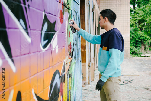 Young man graffiti artist painting on the wall - 221145425