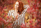 Smiling redhead outdoors backlit by sun, fashion shoot. Close up woman portrait . redhair girl. Beautiful young woman close-up in autumn . - 221146246