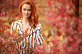 Smiling redhead outdoors backlit by sun, fashion shoot. Close up woman portrait . redhair girl. Beautiful young woman close-up in autumn . - 221146268