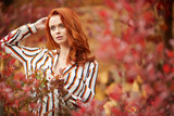Smiling redhead outdoors backlit by sun, fashion shoot. Close up woman portrait . redhair girl. Beautiful young woman close-up in autumn . - 221146295