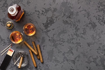 Two glasses with cognac, bottle and cigars © Prostock-studio