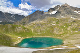 blue lake in high alpine mountain under cloudy sky