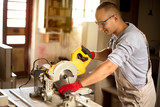Skilled carpenter cutting a piece of wood in his woodwork workshop, using a circular saw - 221154420