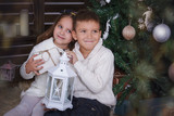 Sister and brother sitting under Christmas tree with gifts - 221156619
