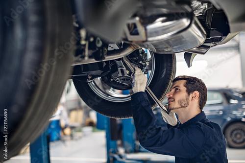 Auto car repair service center. Mechanic examining car suspension - 221156690