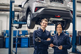 Auto car repair service center. Two happy mechanics - man and woman standing by the car - 221157034