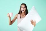 Young girl with white pillow and cup on mint background - 221158658