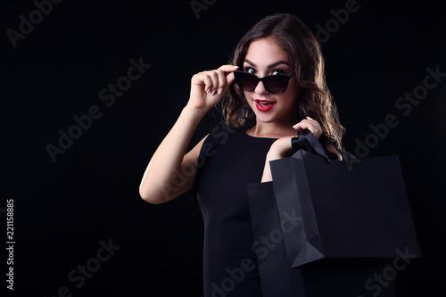 Leinwandbild Motiv Happy woman with shopping bags on black background