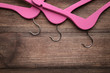 Pink hangers on brown wooden table