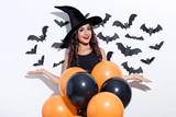 Young woman in halloween costume with balloons on white background - 221159032