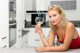 beautiful young blonde woman with red dress drinking white wine - 221159602