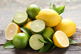 Lemons and limes with green leafs on grey wooden table - 221159659