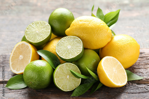 Leinwanddruck Bild Lemons and limes with green leafs on grey wooden table