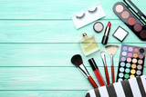 Makeup cosmetics with perfume bottle on mint wooden table