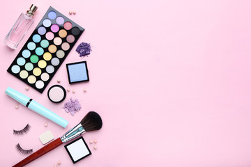 Different makeup cosmetics with perfume bottle on pink background © 5second