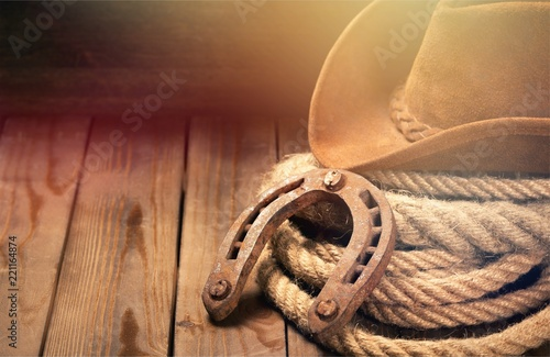 Old horseshoe , lariat lasso and cowboy hat on background