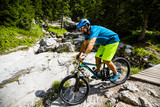 Tourist cycling in Cortina d'Ampezzo, stunning rocky mountains on the background. Man riding MTB enduro flow trail. South Tyrol province of Italy, Dolomites. - 221173690