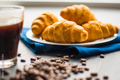 Sticker Macro shot of fresh croissants and coffee on a black background. The concept of breakfast. Dessert and coffee beans. Mate moody color.