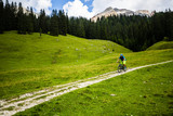 Tourist cycling in Cortina d'Ampezzo, stunning rocky mountains on the background. Man riding MTB enduro flow trail. South Tyrol province of Italy, Dolomites. - 221173815