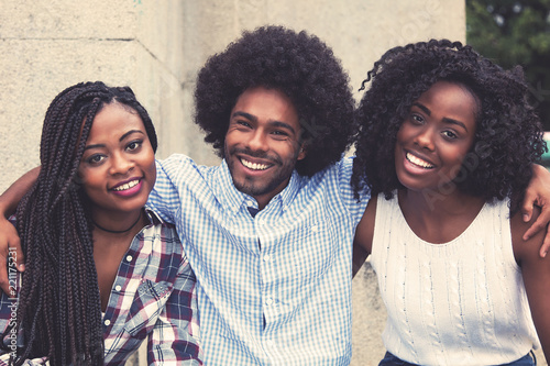 Fototapeta Laughing african american hipster man with two beautiful woman