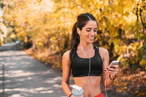 Female athlete smiling and looking at her phone.