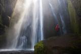 Viajero con abrigo rojo entusiasmado en la cascada oculta Gljufrafossl en Islandia
