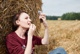 the girl sits near a haystack and paints her lips with lipstick - 221188612