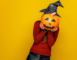 woman holding sad jack-o-lantern pumpkin in front of face - 221193602