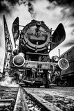 Steamy and rolling old locomotive with red steel wheels on on-site shunting platform, authentic industrial details and craftsmanship along the rail way and train station - 221205673