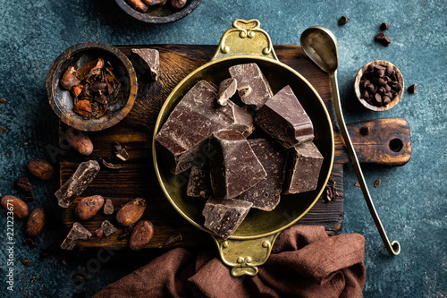 Dark chocolate pieces crushed and cocoa beans. Chocolate background - 221223671
