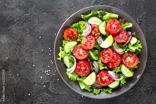 Leinwandbild Motiv Salad. Fresh vegetable salad with tomato, cucumber, lettuce and red onion