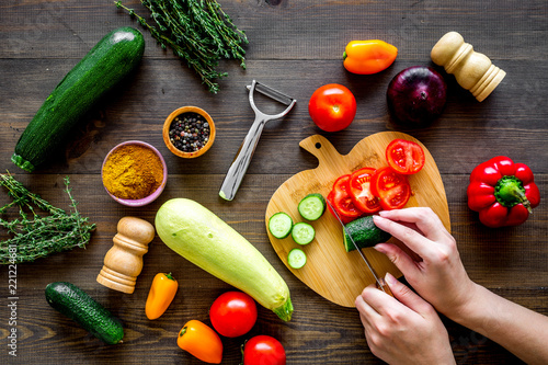 Poster Cut different fresh vegetables on cutting board for cooking vegetable stew. Dark wooden background top view
