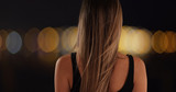 Rear view of athletic woman looking at out of focus lights - 221225690