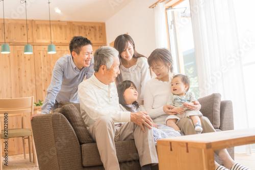 Foto Murales リビングのソファで微笑む3世代家族