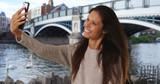 Millennial woman in England stands by Windsor Town Bridge taking selfie - 221229013