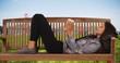 Hipster girl in jean jacket lies on park bench near Golden Gate bridge wondering