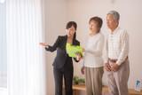 住宅を内見するシニア夫婦と不動産会社のビジネスウーマン - 221233803