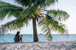 Young women sitting under palm tree using her cell phone at Zen Beach during sunset. Beach Photography. Tropical weather with a passenger boat passing by in the sea. - 221237290