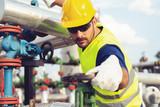Oil worker turning valve on oil rig - 221243008