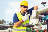 Worker in the oil field talking on the radio - 221243014
