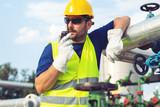 Worker in the oil field talking on the radio - 221243035
