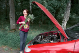 a young girl is near a broken car and gives him flowers - 221245428