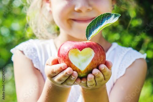 Leinwandbild Motiv Child with an apple. Selective focus. Garden.