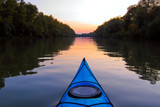 Bow of blue kayak on Danube river at dusk. Kayaking on calm autumn river in the evening. View on river from the bow of kayak - 221245808